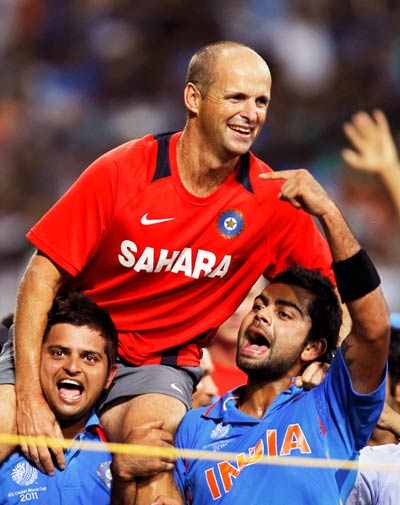 Suresh Raina and Virat Kohli (R) carry Coach Gary Kirsten during celebrations. ? Photo by Reuters