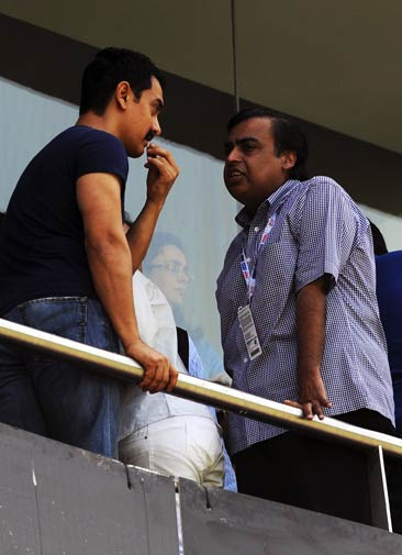 Indian actor Aamir Khan (L) and industrialist Mukesh Ambani interact in the stands during the match. ? Photo by AFP