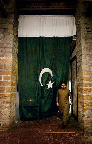 Ashraf Kalim - one of the organisers - walks into the spacious warehouse-gallery. A huge flag was hung like a curtain in the entrance.