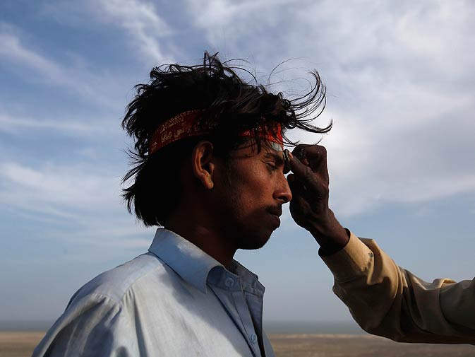 A devotee is dabbed with sacred volcano mud as a spot on his forehead.