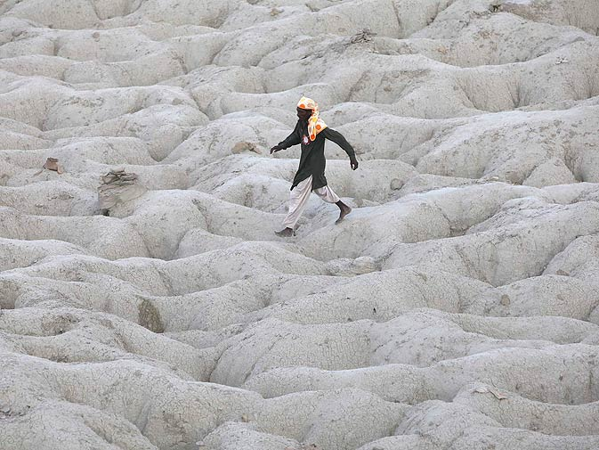 A devotee walks on the surface of a mud volcano to perform a ritual offering of coconuts.