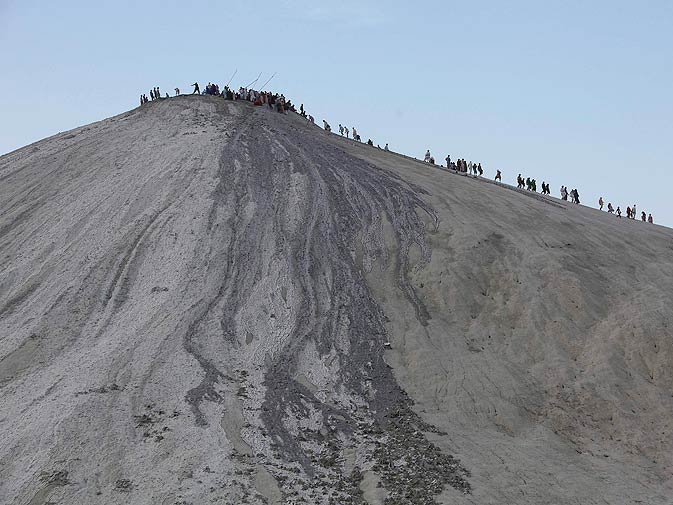 Devotees walk on a mud volcano to perform a ritual offering of coconuts.
