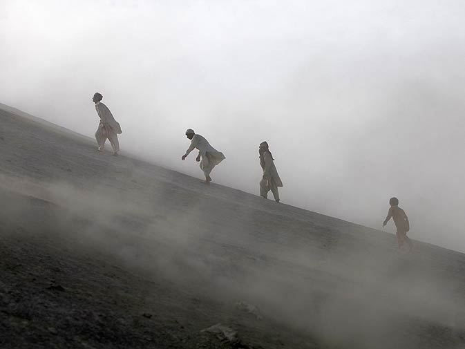 Devotees climb a mud volcano to perform a ritual.
