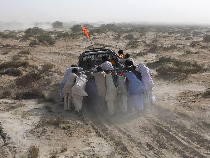 Devotees push a vehicle stranded in desert while visiting Shri Hinglaj Mata Temple.