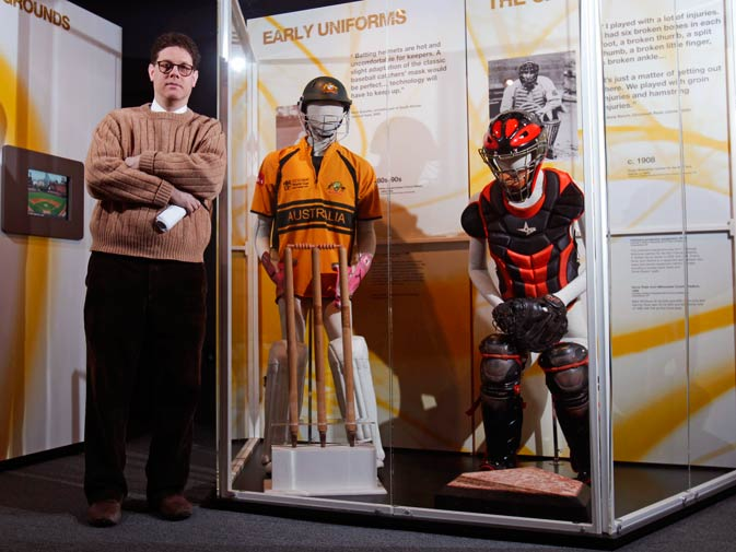 Senior Curator Tom Shieber poses with uniforms worn by a cricket wicketkeeper, left, and a baseball catcher.