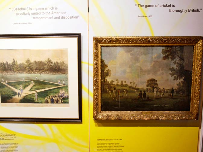 This photo shows a baseball painting, left, and a cricket painting on display at the exhibition.