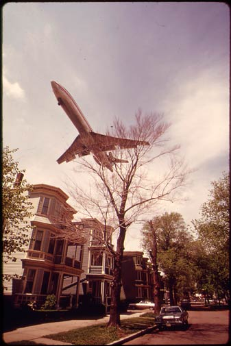 In this May 1973 photo provided by the US National Archives, a jetliner passes above a Boston neighborhood near Logan International Airport.