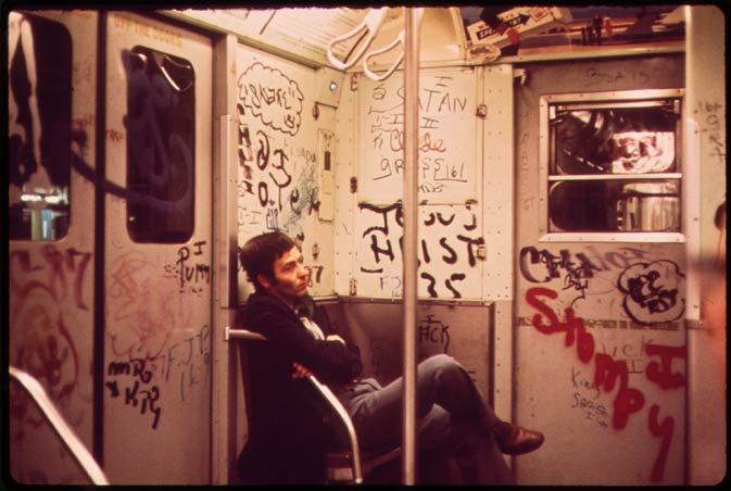 In this May 1973 photo, an unidentified man rides a graffiti-covered subway in New York.