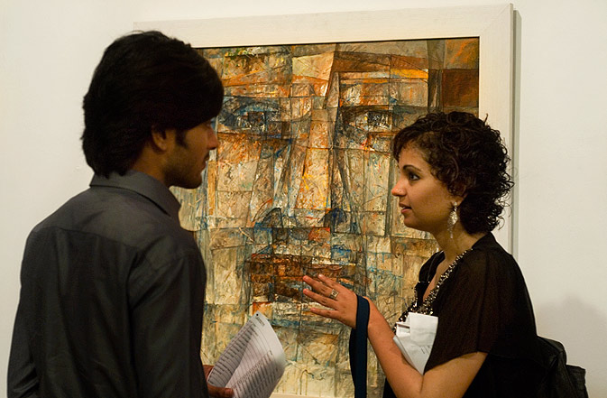 Marvi Malik - one of the artists, discusses Farukh Shahab's abstract portrait (pictured in the background) with a visitor.