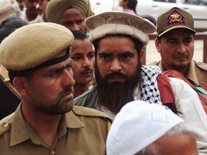 Indian police personnel escort Mohammad Shokat before crossing over to Pakistan.
