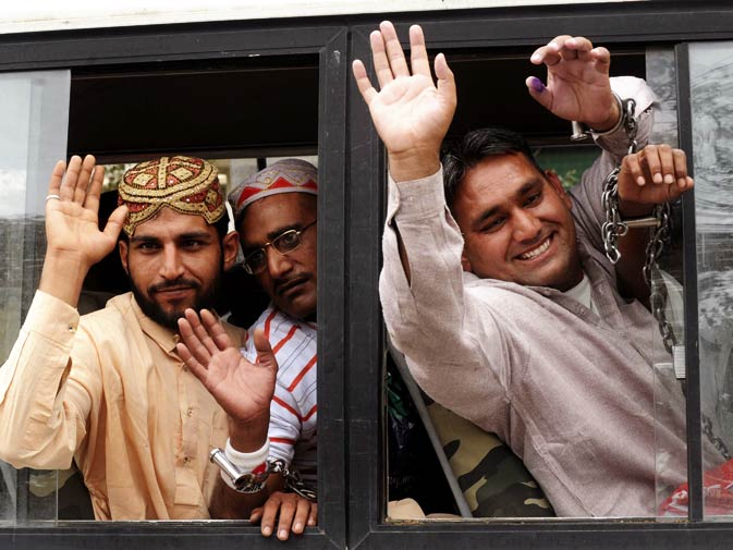 Released Pakistani prisoners Imran Khan (L), Mohammad Akram (C) Mohammad Toker (R) wave as they reach the Wagah Border Post.