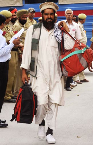 Mohammad Shokat (C) crosses over to Pakistan with his baggage.