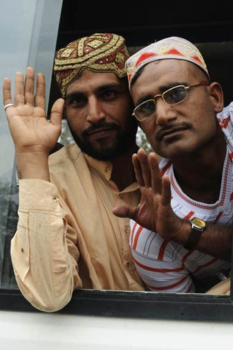 Imran Khan (L) Mohammad Akram (R) gesture as they come back to Pakistan.