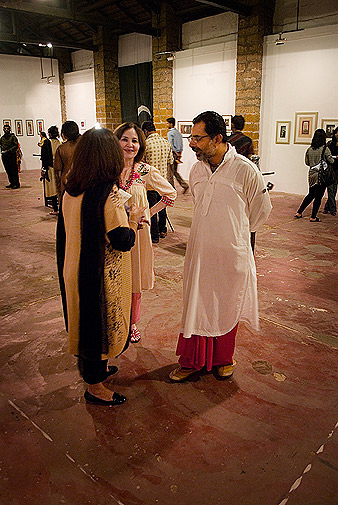 "Yousuf Bashir, the curator of the exhibition, chats with visitors. Bashir is the owner of the Commune and also contributed his own paintings as well as an installation titled ""Mazloom Tawaif""."