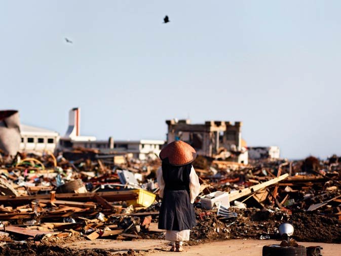 A Japanese Buddhist monk prays at a devastated area. – Photo by AP