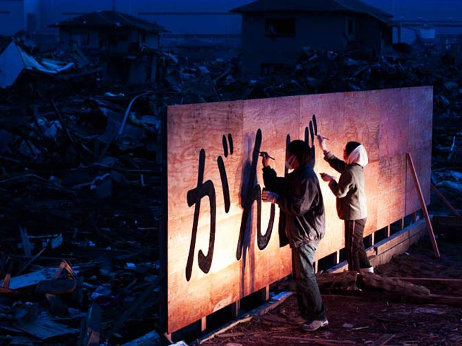 """Tsunami survivor Tadao Kamei (L) and a friend draw the words """"Ganbaro!"""" or """"hang in there"""" on a recycle billboard. – Photo by AFP"""