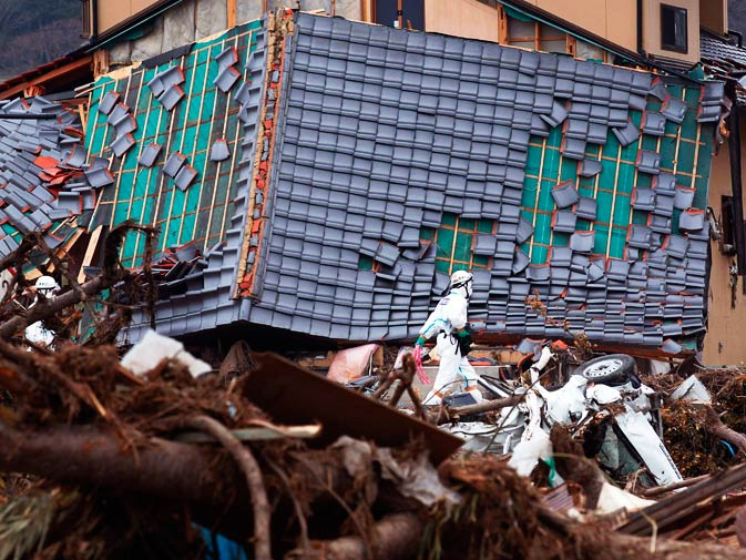 A police officer walks past a damaged house while searching for bodies. – Photo by Reuters