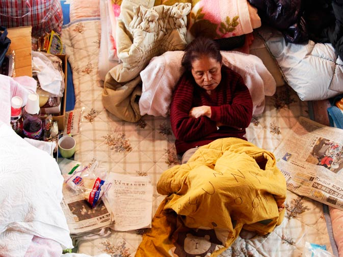 A survivor rests in an emergency shelter. – Photo by AP