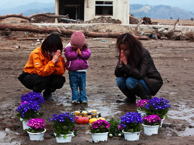 Two-year-old Ayaka (C) and family members pray for her missing grandmother and great-grandmother at a vacant lot where they lived. – Photo by AFP