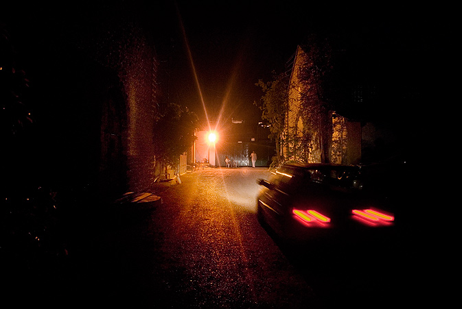 A car drives out through the Commune's dark compound at night after the exhibition.