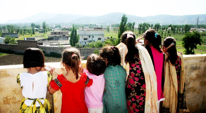 Everyone wants to catch a view. These children look out from their high vantage point, to see the compound of Osama bin Laden in Abbottabad, Pakistan.