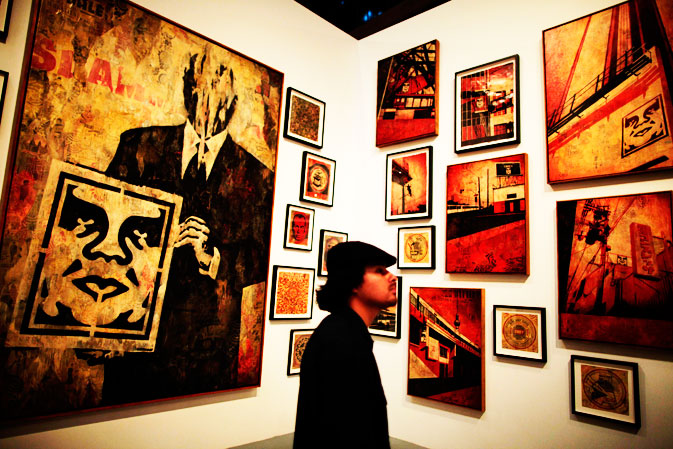 A man views works by Shepard Fairey at the exhibit.