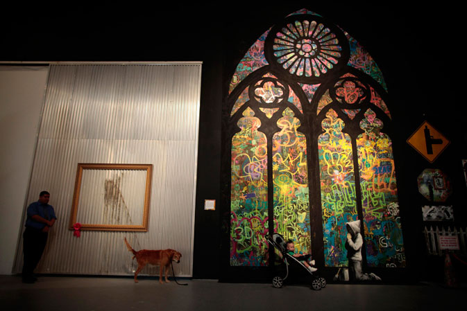 A security guard watches as a man poses his son next to a Banksy stained glass window at the exhibit.