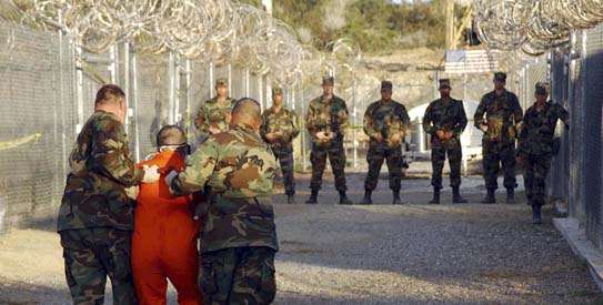 US Army Military Police escort a detainee to his cell during in-processing to the temporary detention facility at Camp X-Ray in Naval Base Guantanamo Bay- Reuters 2002