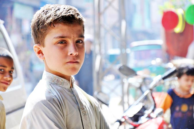A child with a solemn expression pauses for the camera while accompanying other children in the marketplace.
