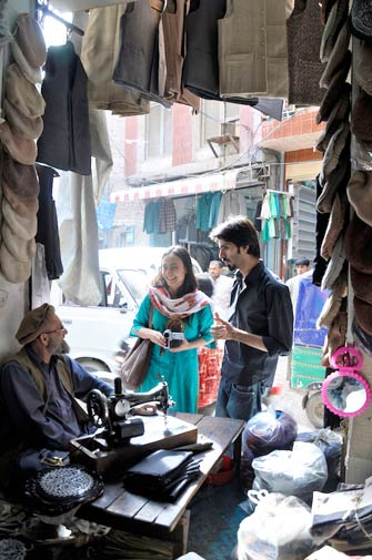 Journalist from Italy, Vivianna Mazza, in conversation with the Chitrali cap seller. Vivianna is accompanied by Yasir Khan, a musician from the band, Yasir and Jawad.