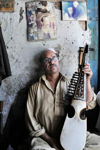 Mushtaq Hussain's grandfather migrated from Afghanistan and introduced the lute-like instrument in Pakistan. According to Mushtaq, he was given an award by then Pakistani President, Ghulam Ishaq Khan, for his work. In the background is a photo of his grandfather receiving the award as well as a collage of photos of Mushtaq as a rabab player.