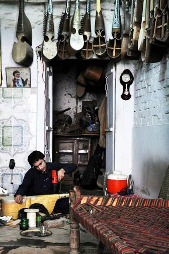 Khurram Shahzad, 23, drills a hole in a rabab he is making. He is Mushtaq Hussain's nephew and his shop is located off the main street.