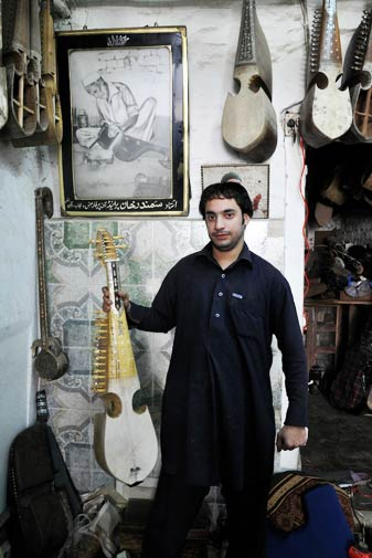 Khurram Shahzad poses with a rabab he is making in front of his ancestor, Samandar Khan's portrait.