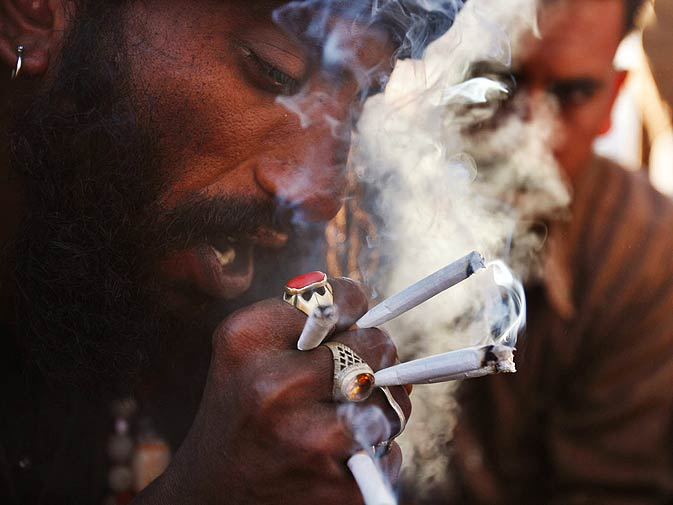 A man smokes up cannabis at a local shrine in Punjab. – Photo by Arif Ali/White Star