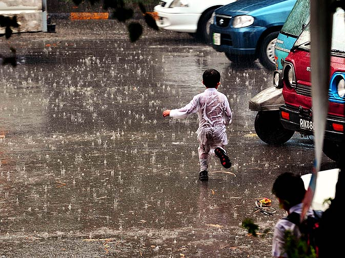 A care-free boy runs across the road as it rains in Lahore. – Photo by Arif Ali/White Star