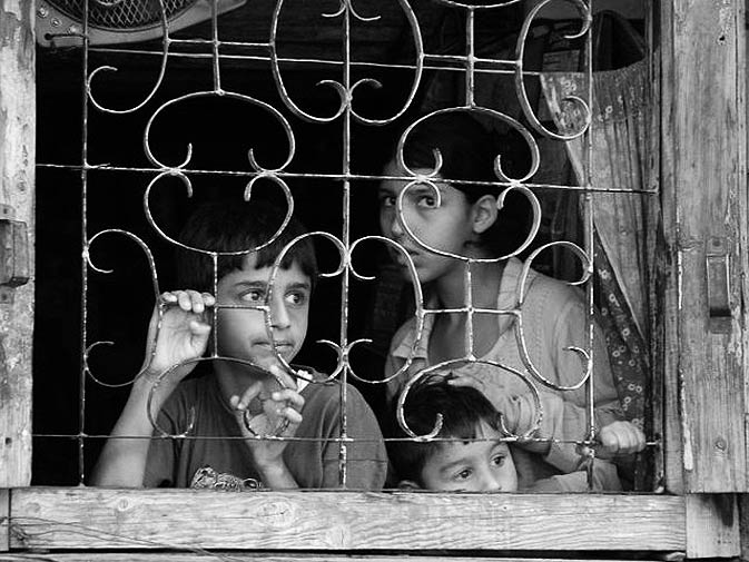 Kashmiri young boys peer out of an iron-grilled window. – Photo by Dilnaz Boga/Herald