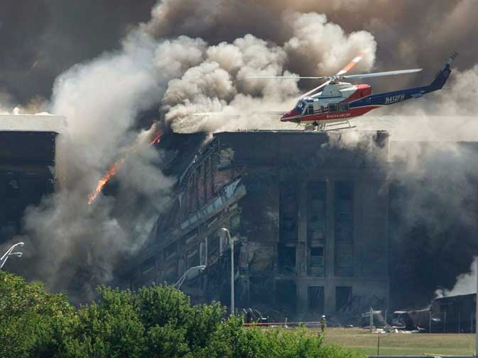 A rescue helicopter surveys damage to the Pentagon as firefighters battle flames after an airplane crashed into the US military Headquarters outside of Washington in this September 11, 2001 file photo.  Bin Laden was named principal suspect for coordinating the attacks in New York and Washington and Washington offered a 25-million-dollar reward for any information leading to the arrest of bin Laden.? Reuters  (File Photo)