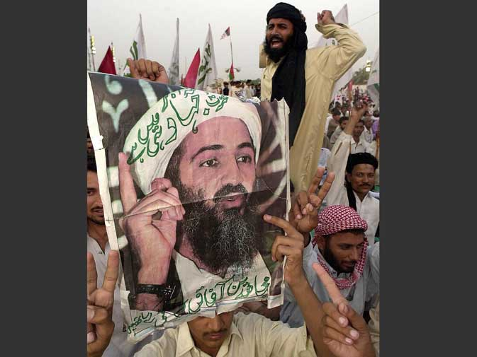 Supporters of Pakistan's Jamiat Ulema-i-Islam, known for its close ties with the ousted Afghan Taliban, attends an election campaign rally of the Mutahidda Mujlis-e-Amal, while holding portraits of US most wanted chief of al Qaeda network Osama bin Laden in the southwestern city of Quetta on October 7, 2002. ? AFP (File Photo)