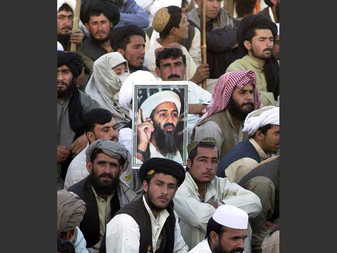 An activist carries a portrait of wanted terrorist Osama bin Laden while another shouts anti-US slogans during a demonstration in Karachi on October 7, 2001.  On October 7, US-led strikes on Afghanistan begin, aimed at forcing the ruling Taliban to hand over bin Laden. Bin Laden vows no peace for the US and its citizens in a message broadcast via the Al-Jazeera television network. ? AFP (File Photo)