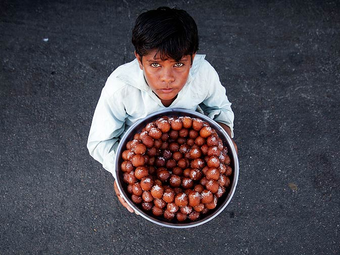 12-year-old Naeem sells gulab jamun in the streets of Karachi, to earn about 300 Pakistani Rupees ($3.50) per day. ? Photo by Reuters