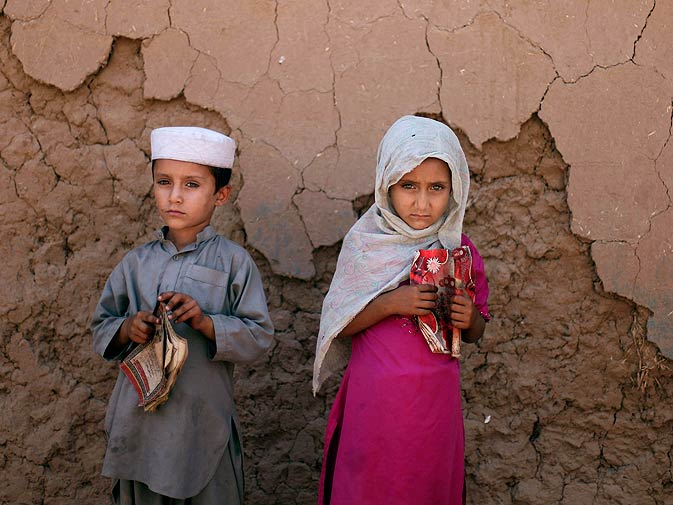 Nazmeena Asghar, 6-year-old, and her brother Heyyat, 5-year-old, wait for their Islamic religious lesson in a slum area at the outskirts of Islamabad. ? Photo by AP