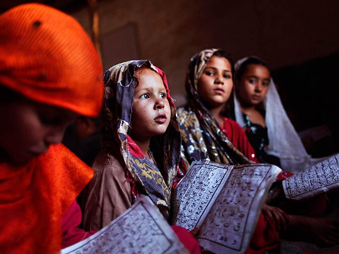 Slum children attend an Islamic religious class at the outskirts of Islamabad. ? Photo by AP