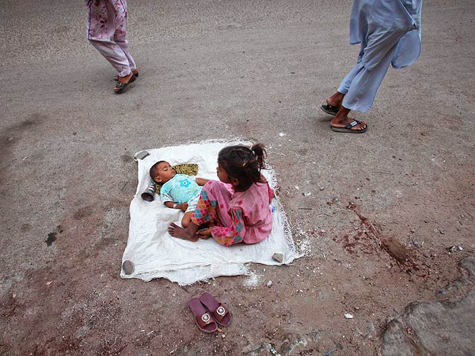 Radha sits beside her two-year-old sister Kiran as they beg along the busy street in Karachi. ? Photo by Reuters