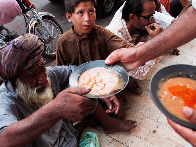 Free food is distributed to the poor by a non-governmental organization in Karachi. ? Photo by AP