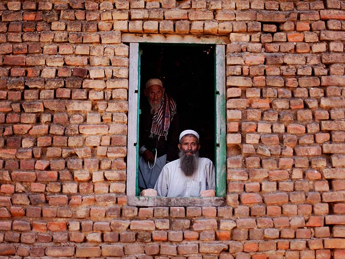 Elderly men look out from a mosque situated in a slum area. ? Photo by AP