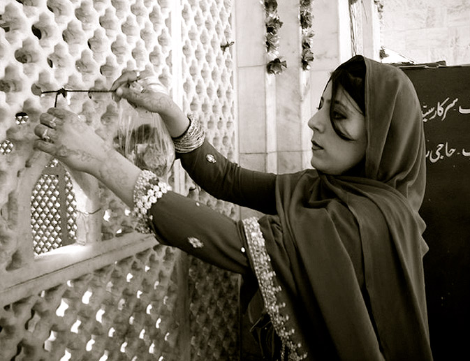 A woman is seen praying outside the tomb of Bulleh shah. She is tying a mannat ka dhaga (a ritual wish string)  to the wall, available outside the tomb.