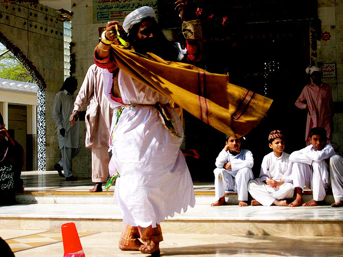 A malang dancing to a Sufi kal?m being sung by other malangs at Bulleh Shah's shrine. Music and dance are acts of devotion to the patron saints and are representative of how the malangs have surrendered everything material to find inner peace.