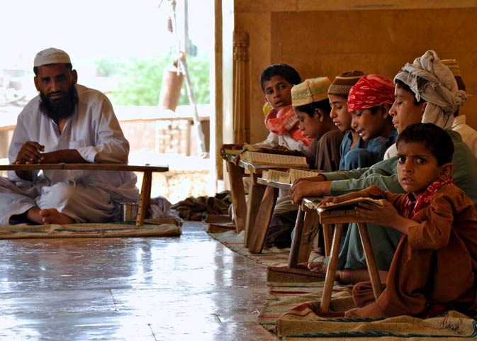 A Qari at the Derawar Mosque giving lessons on how to read the Quran to children from the neighbouring village. The children keep their copies of the Quran on small, primitive wooden stools.