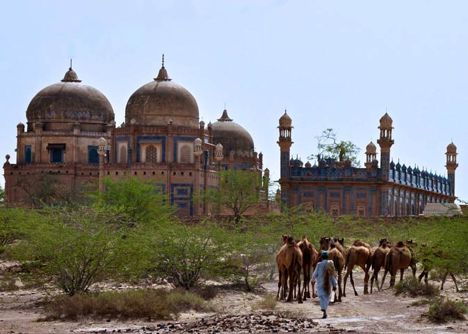 A camel herder leads his camels through the front of the royal graveyard of the Abbasi family. The Abbasi family was the ruling Nawab family of Bahawalpur and all of the previous Nawabs are buried here. The graveyard is still owned and controlled by the Nawabs? surviving family members. The monument is located near and opposite to the Derawar Fort.