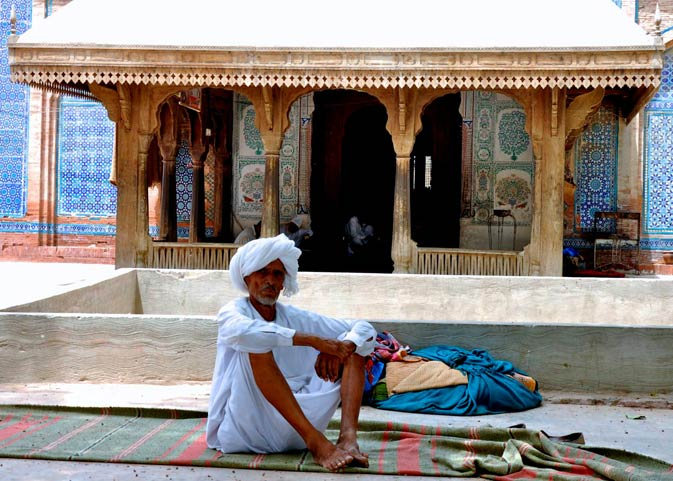 A man frequenting the shrine sits in front of the entrance leading to the darbar of Jalaluddin Bukhari.